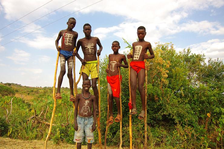 竹馬に乗って全身ペイントしているバンナン族
